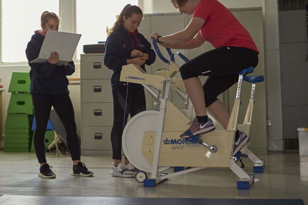 Female working on an exercise bike - two other females spectating and taking notes