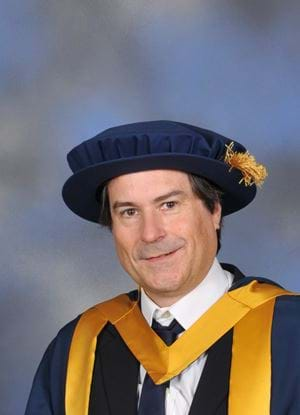 A photo of David Braben in graduation outfit