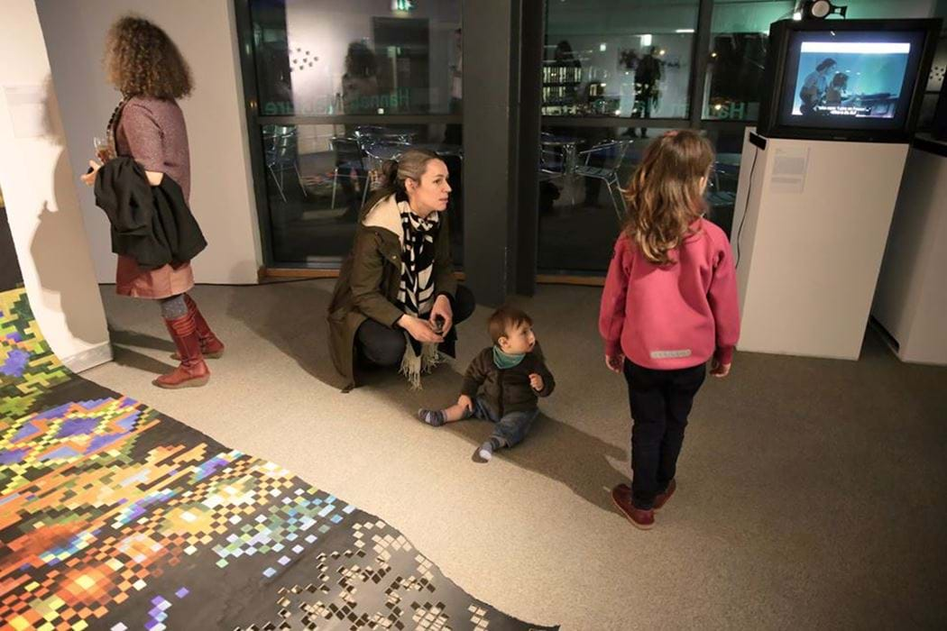 Female and 2 small children looking at art