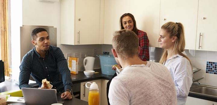 Group of four young adults huddled around in a kitchen, two girls and two guys. One of the guys is eating a sandwich.