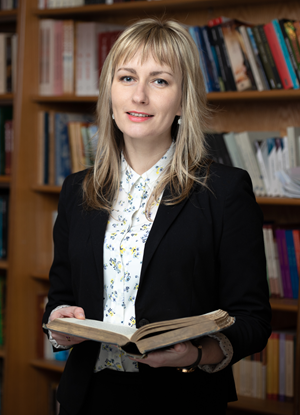 Graduate standing in front of bookshelf holding a book