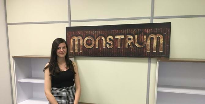 A picture of Stephanie Bayzeley by the logo for the game Monstrum