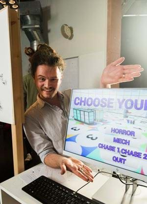 "Picture of Cameron Moody presenting a project, gesturing towards a monitor with the words ""Choose your game: Horror, Mech, Chase 1, Chase 2, Quit"" on it."