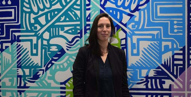 Picture of Sarah Quenel smiling, she is standing in front of a wall painted with a colourful pattern