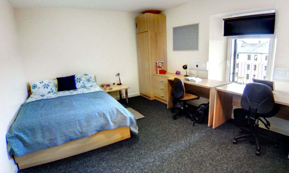 bedroom with double bed, wardrobe, 2 desks and 2 chairs