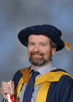 A picture of Michael Lamb holding his honorary degree