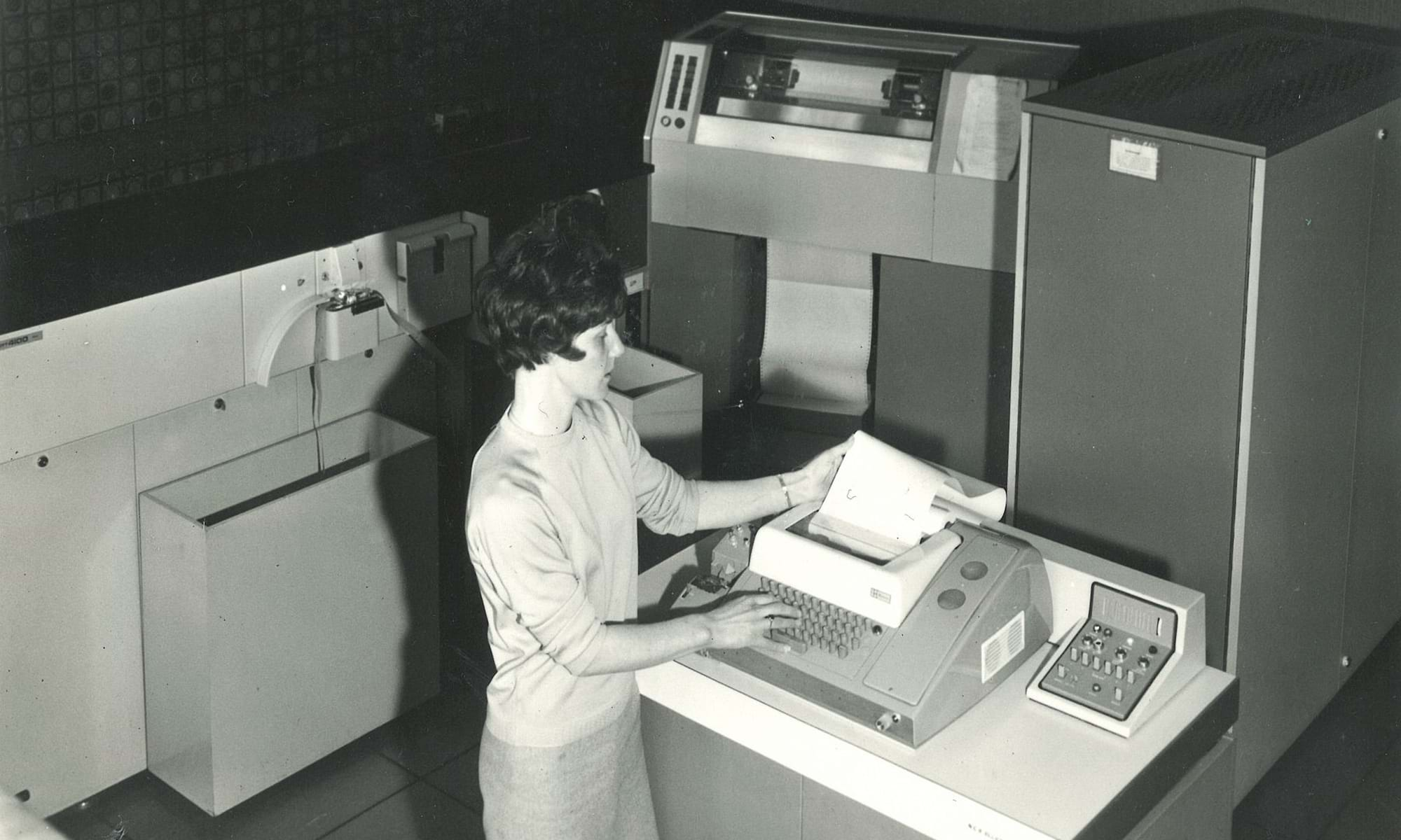 Female staff member at Dundee Institute of Art and Technology (Abertay University) looking at data being printed from a computer in the 1960s