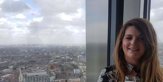 A picture of Linzi Brechin holding a glass of champagne with the view of a large city behind her.
