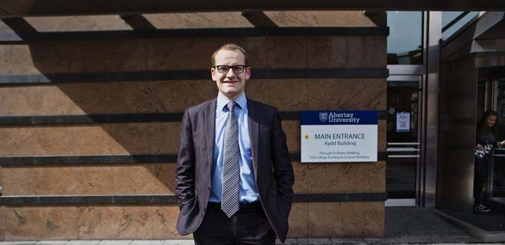 Steven Traynor in a suit standing in front of Abertay University's Kydd building