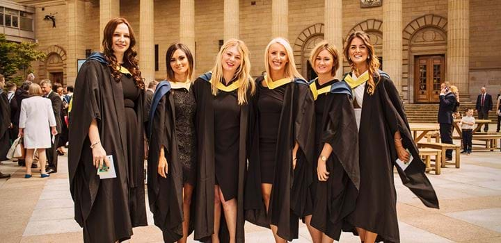 Group of female students wearing graduation gowns