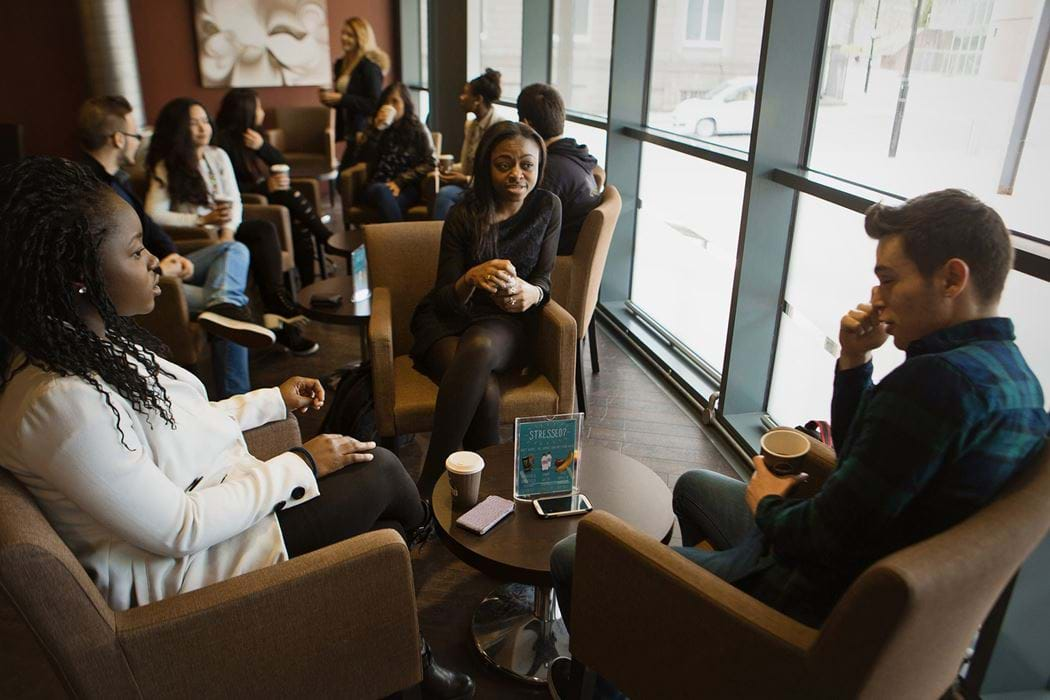 Group of people sitting chatting in a coffee shop