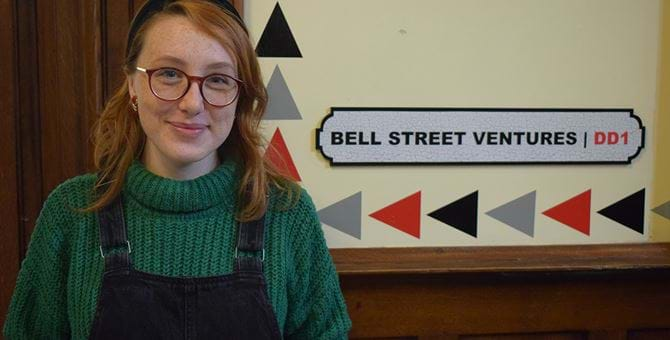 "A picture of Stephanie Crowe standing in front of a sign with the words ""Bell Street Ventures"" on it."