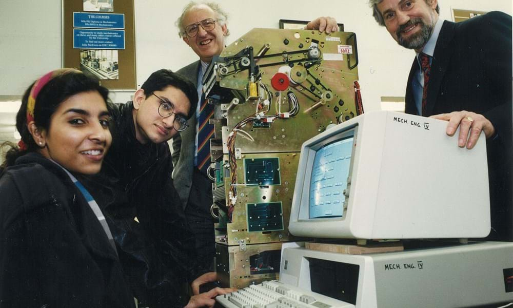 Two students, female and male, with two male lecturers in the mechanical engineering department of Dundee Institute of Technology (Abertay University) with a built ATM machine (inner parts only) and desktop computer.