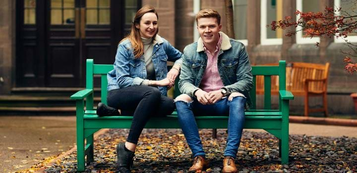 male and female sitting on a bench