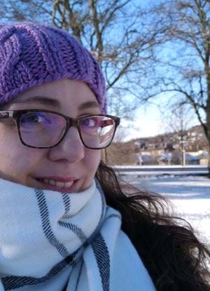 Picture of Maria smiling, in the background is snow covered ground