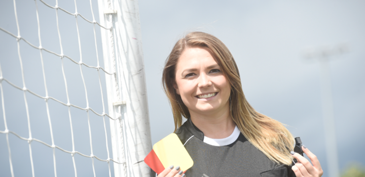 Vikki in FIFA Assistant Referee uniform holding a whistle and cards