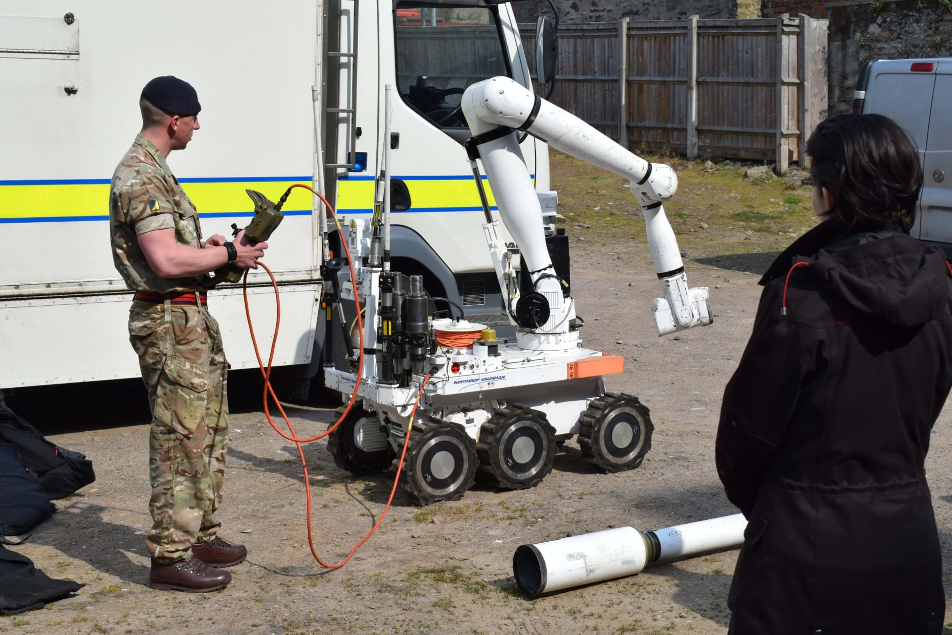 A member of the bomb disposal unit using the bomb disposal robot in front of students