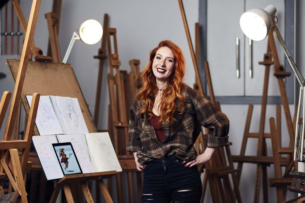 A female standing in front of an art easel