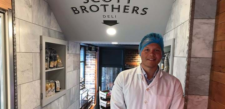 A picture of Samuel Ceolin wearing a hairnet and apron at Scott Brothers Butcher