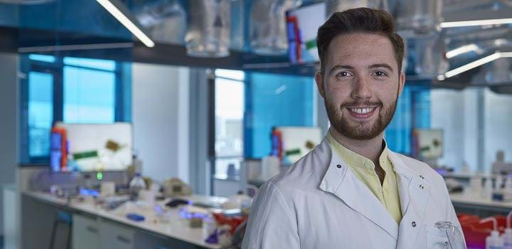 Smiling male standing in a science laboratory