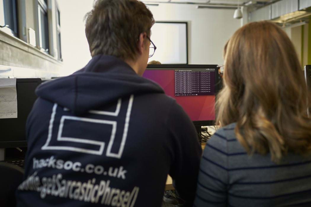 Picture of male and female from behind - male is wearing an Ethical Hacking Society hoody