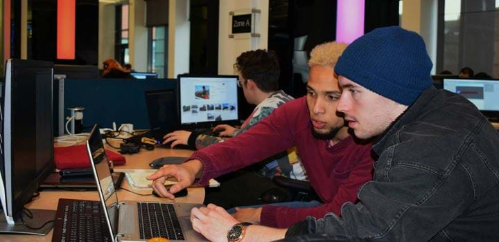Two males working together on a Desktop computer