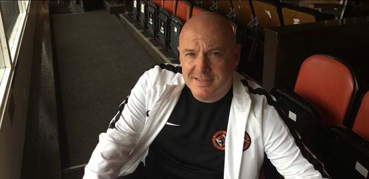 A photo of Joe Rice sitting in the stands at Tannadice
