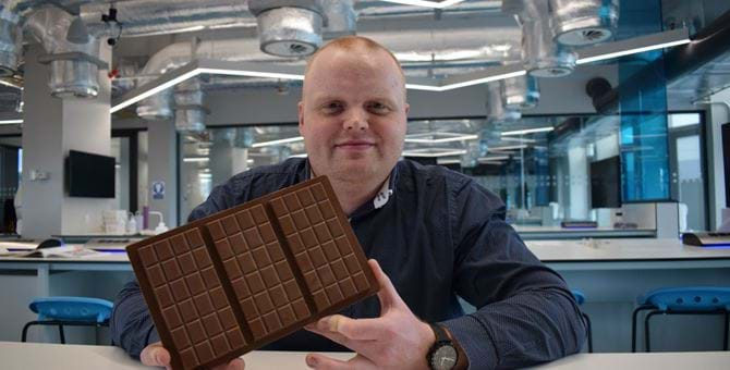 Male holding a very large bar of chocolate