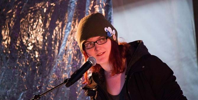 A photo of Natalie Clayton in front of a microphone