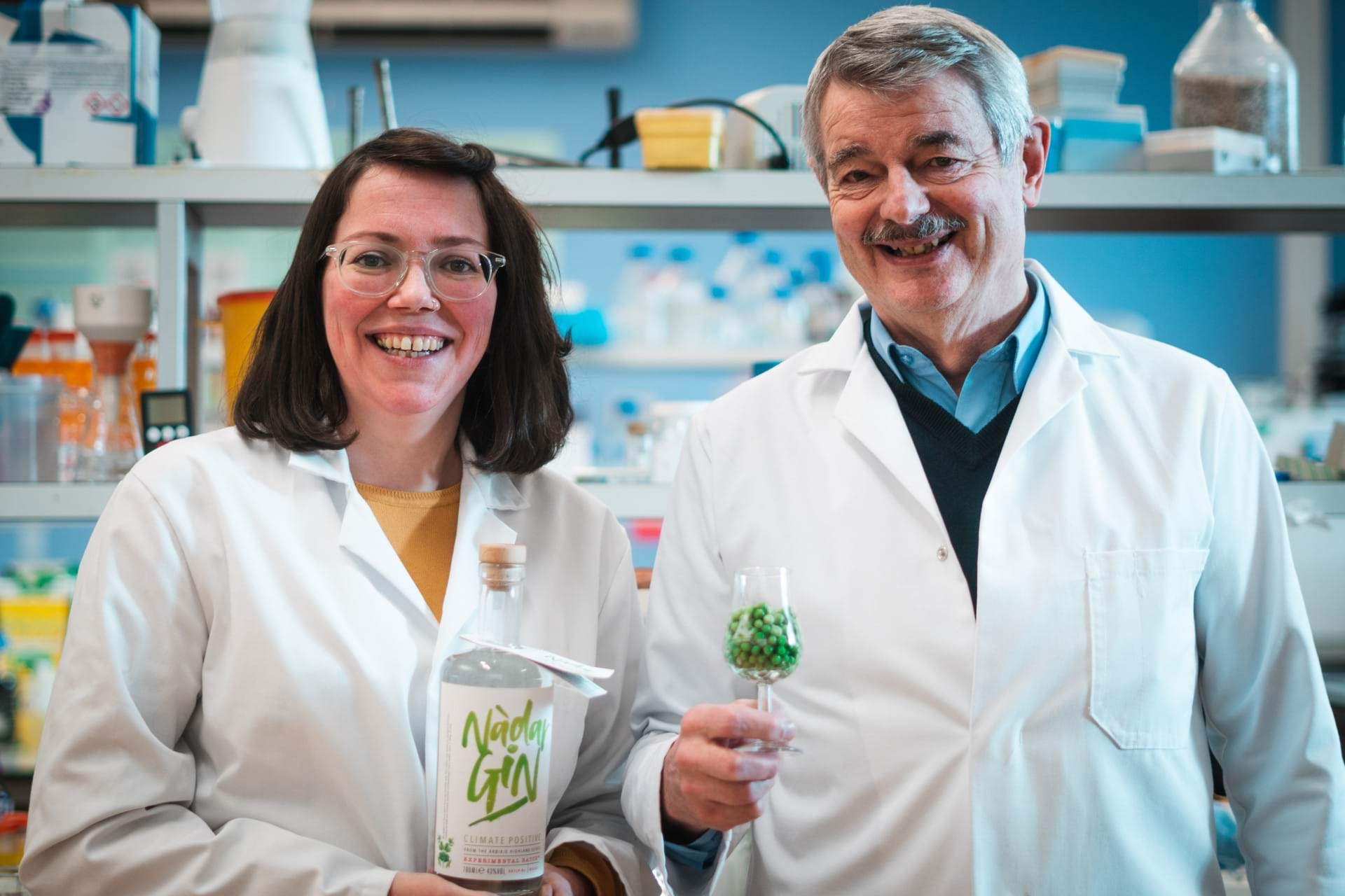 Kirsty Black and Graeme Walker holding a bottle of Nadar Gin and a glass of peas