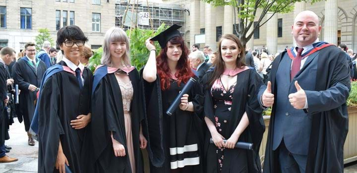 Group of graduates wearing robes and holding scrolls - 4 females, 1 male