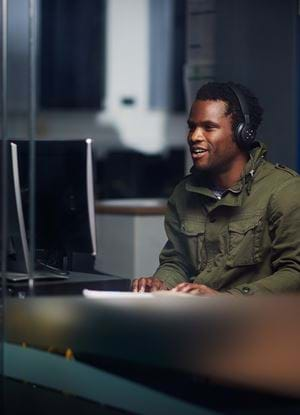 Male student wearing headphones whilst working on a Desktop computer