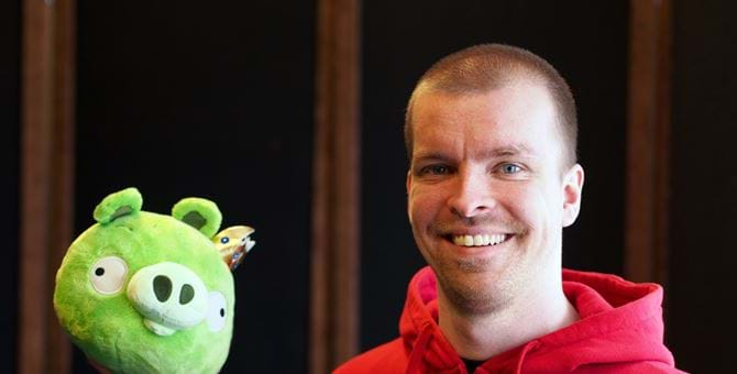 A picture of Pasi Pitkanen holding a stuffed toy of a pig from the game Angry Birds