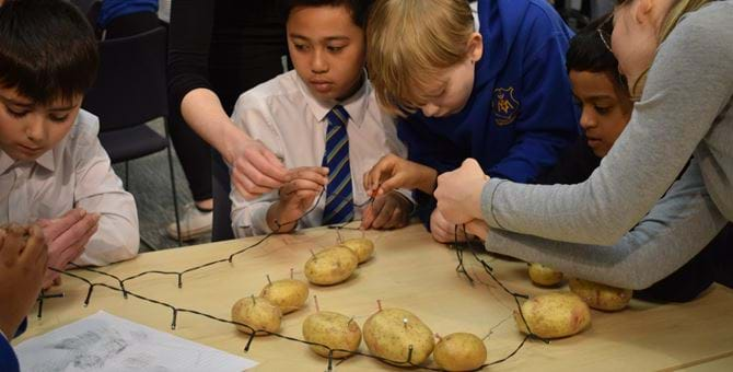 group of school children working together using potatoes and led lights