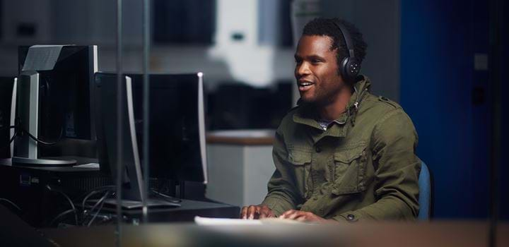 Male wearing headphones and using a Desktop computer