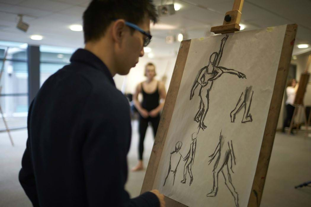 male drawing using an easel - live model in background