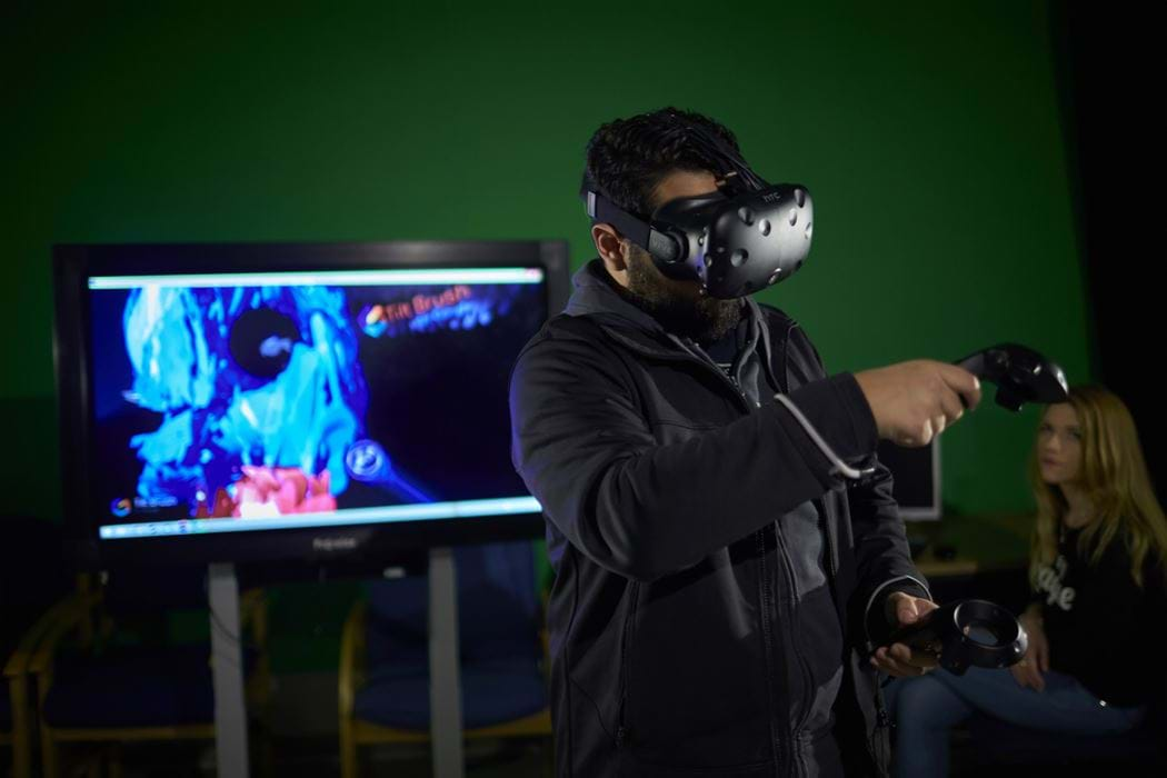 Male wearing Virtual Reality head - female watching in background