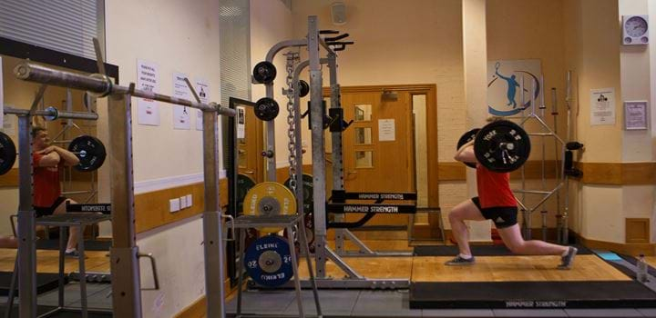 Gym environment - male in a squatting position holding very large weights above his shoulders