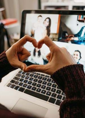 A photo of hands making a heart symbol in front of a laptop