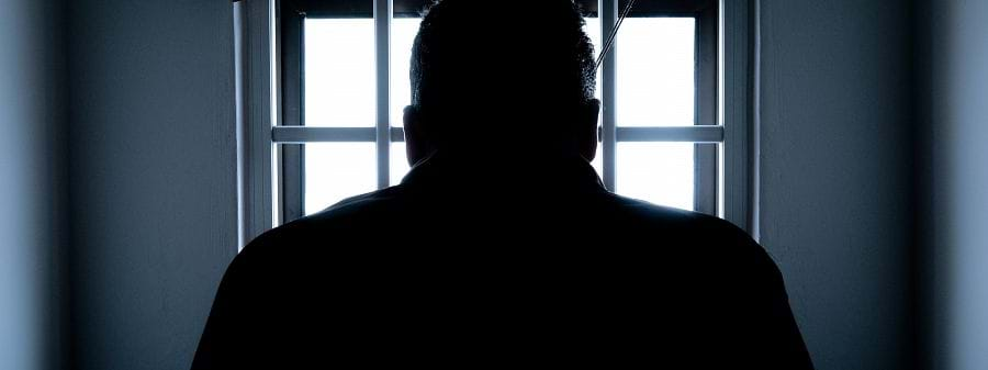 Image shows the silhouette of a man in a prison cell