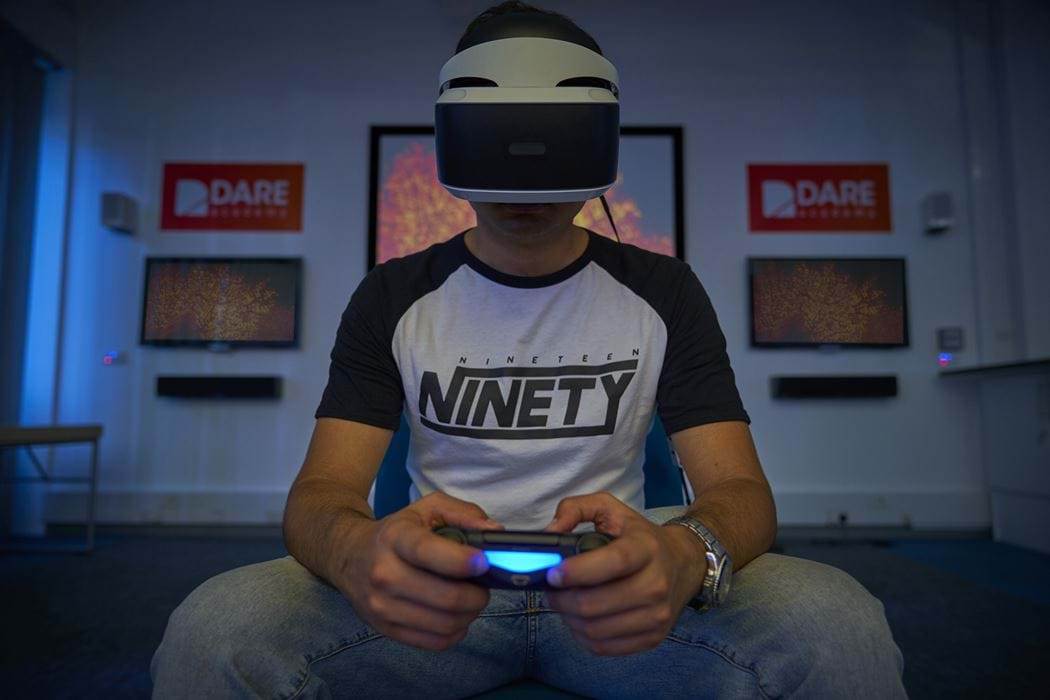 Abertay University Student in a PSVR helmet facing the camera holding a PS4 Controller