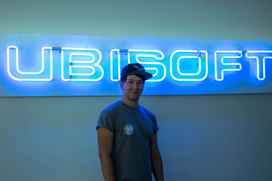 Male wearing a baseball cap standing in front of a Ubisoft sign