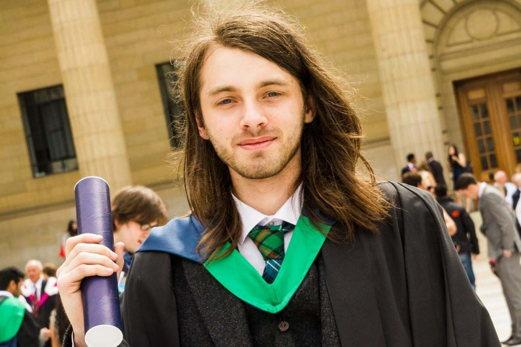 Male wearing graduation robes, holding scroll and smiling