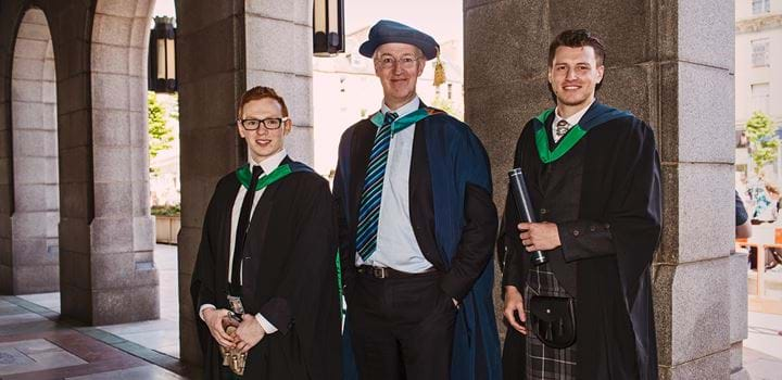 Three males wearing graduation gowns