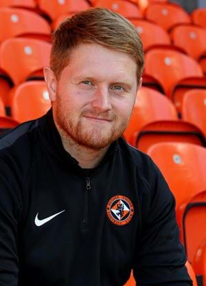 A photo of Michael Malone sat in the stands at Tannadice