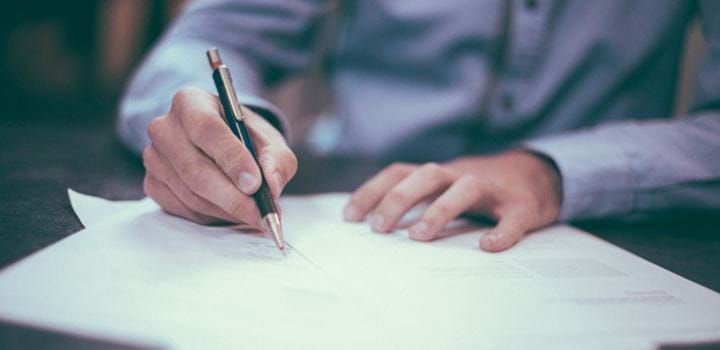 A photo of someone signing papers.