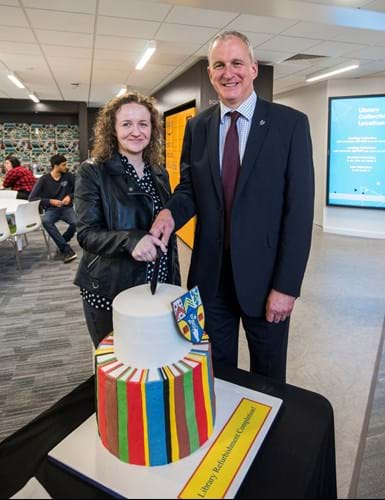Nigel Seaton and Victoria Ryan cut Library reopening ceremony cake.
