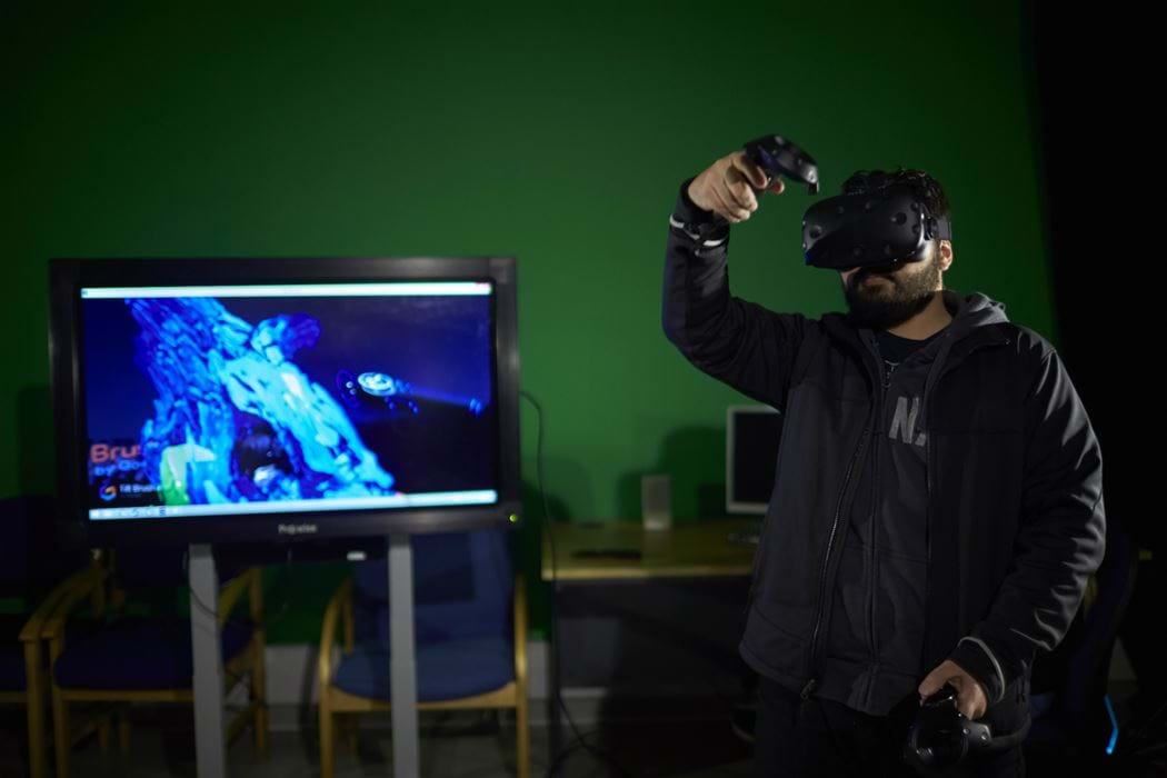 Male wearing Virtual Reality head - display screen in background
