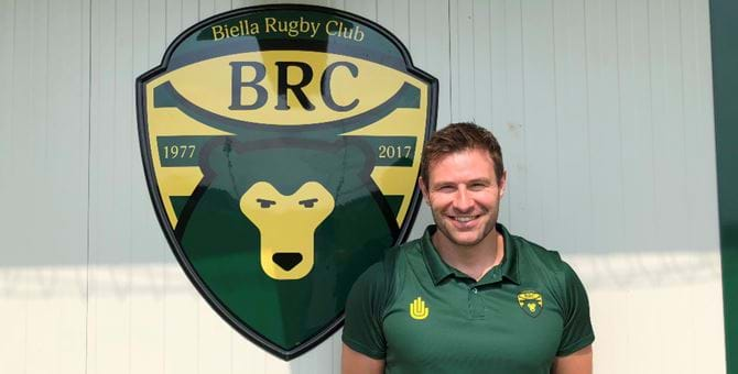 Fraser Murray next to the green and yellow Biella Rugby Club logo wearing a team shirt