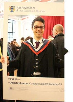 Male wearing graduation robes and holding up large cardboard cut out of a picture frame